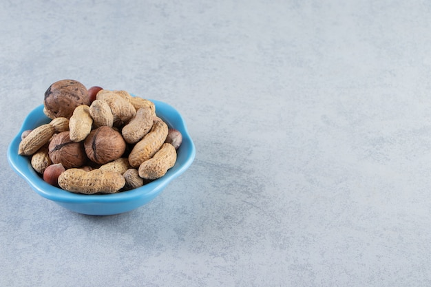 Blue bowl of organic nuts placed on stone background.