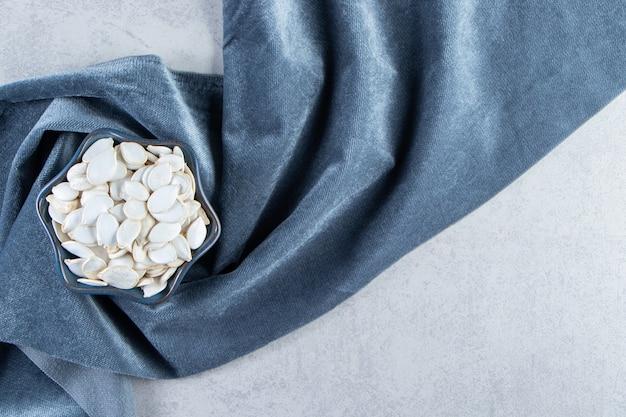 Ciotola blu di semi di zucca con panno blu su sfondo di pietra.