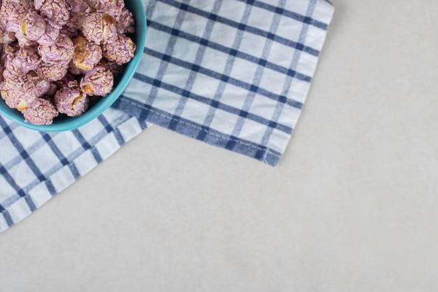 Синяя миска, покоящаяся на сложенном полотенце и наполненная попкорном, покрытым конфетами, на мраморном столе.