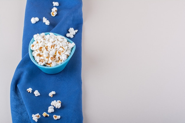 Blue bowl of salted popcorn for movie night on white background. high quality photo