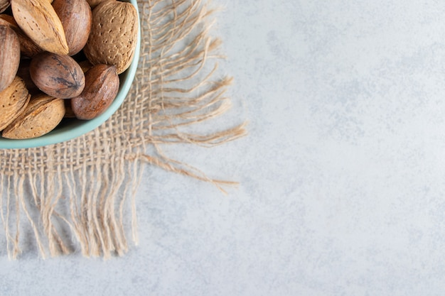 Blue bowl of shelled almonds and walnuts on stone background.