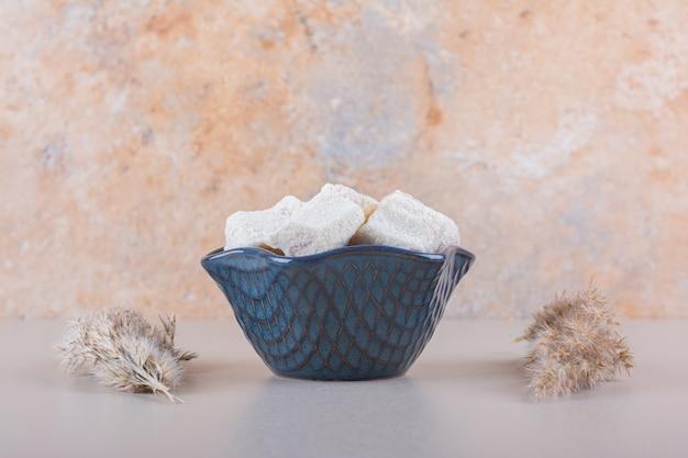 Ciotola blu di dolci con noci su sfondo bianco. foto di alta qualità