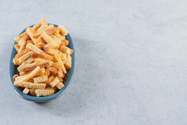 Blue bowl of tasty crispy crackers on stone background.