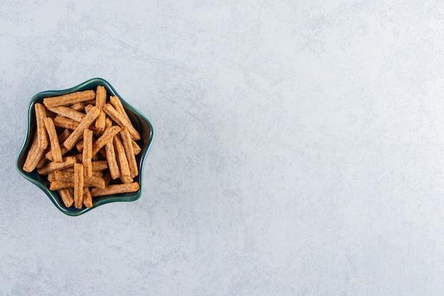 Blue bowl of tasty stick crackers on stone background.