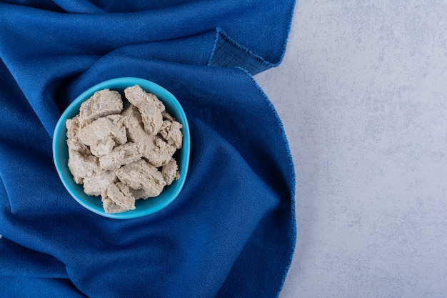Ciotola blu di gustoso halva di girasole su pietra.