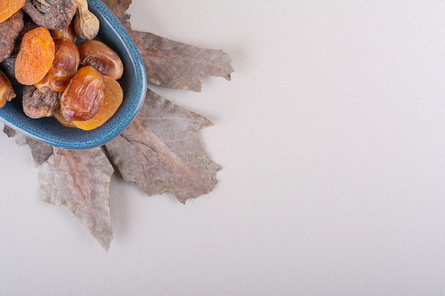 Blue bowl of various organic nuts and fruits on white background. high quality photo