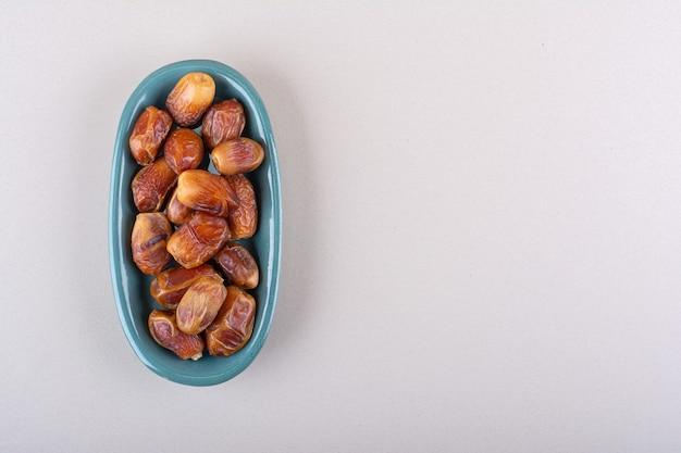 Синяя миска с сушеными вкусными финиками на белом фоне. фото высокого качества