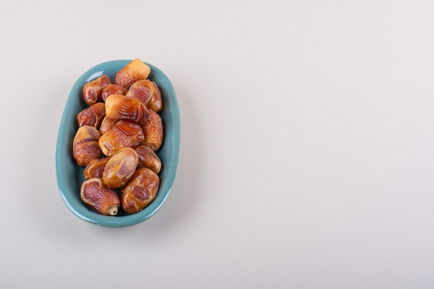 Blue bowl with dried tasty dates on white background. high quality photo