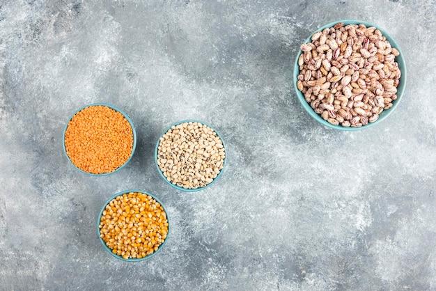 大理石のテーブルにさまざまな豆とトウモロコシが入った青いボウル。