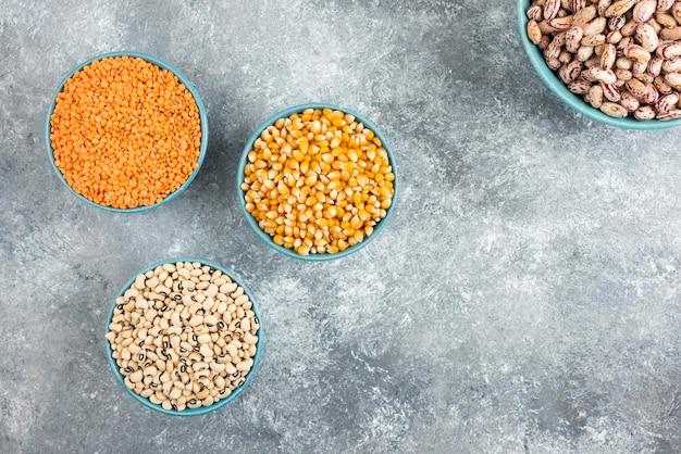 대리석 테이블에 다양 한 콩 및 옥수수의 파란색 그릇.
