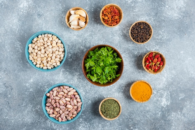 Blue bowls of raw beans and spices on marble background.
