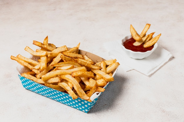 Blue box of french fries with ketchup
