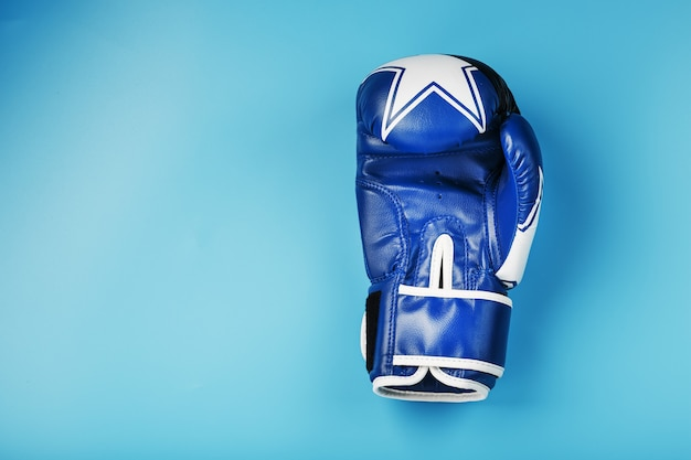 Blue boxing glove on a blue background, free space