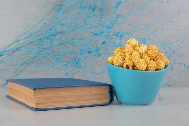 Rami blu, una ciotola di popcorn ricoperto di caramello e un libro sul tavolo di marmo.