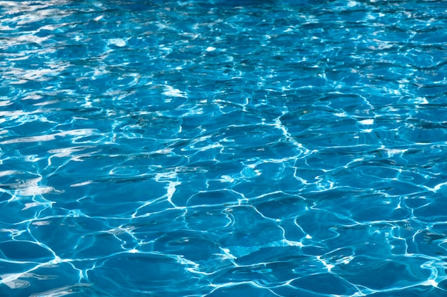 Blue and bright ripple water surface in swimming pool with sun reflection.