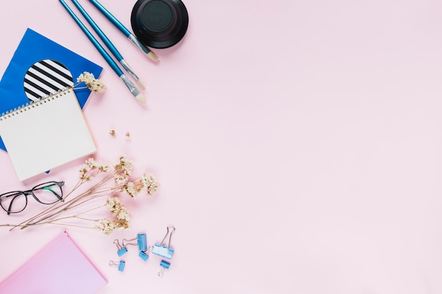 Blue brushes and stationery with white flowers on pink background