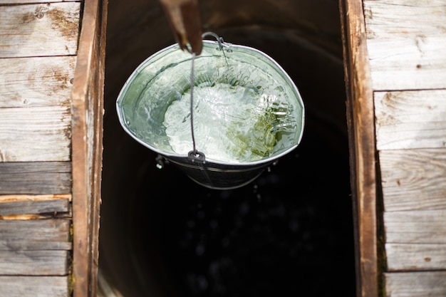 Blue bucked inside water well. a water well with an old iron bucket