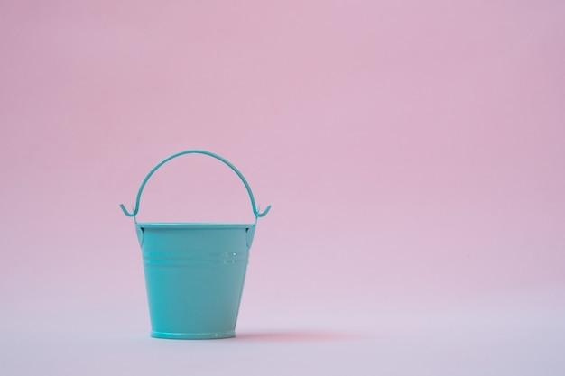 淡いピンクの壁に青いバケツ、ミニマリズム