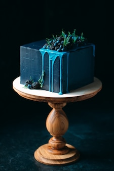 Blue cake decorated with blackberries and blueberries.