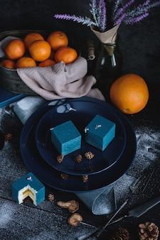 オレンジとみかんを立方体にした青いケーキ。黒いテーブルの近くには、オレンジ、みかん、ナッツの材料があります。素朴なスタイル