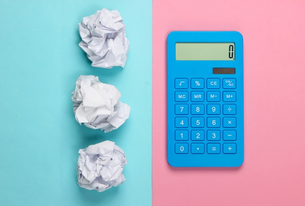 Blue calculator with crumpled balls of paper on bluepink pastel