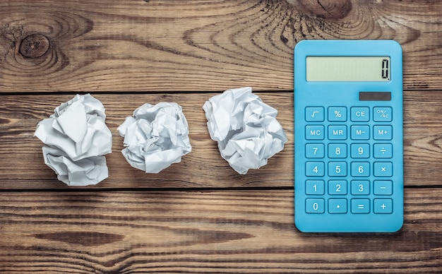 Blue calculator with crumpled paper balls on a wooden table