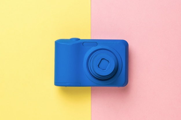 A blue camera on a two-tone yellow and pink background. outdated equipment for photography.