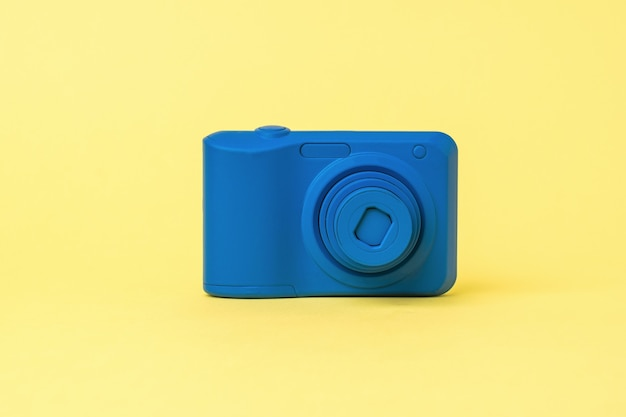 A blue camera with a retractable lens on a yellow background. outdated equipment for photography.