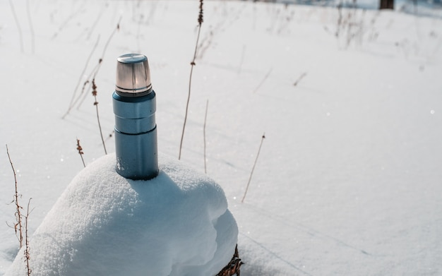 눈 더미에 서있는 블루 캠프 보온병. 겨울 하이킹 개념.