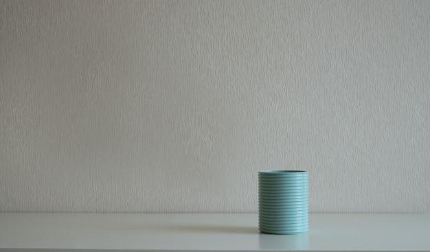 灰色の壁の机の上の青い缶