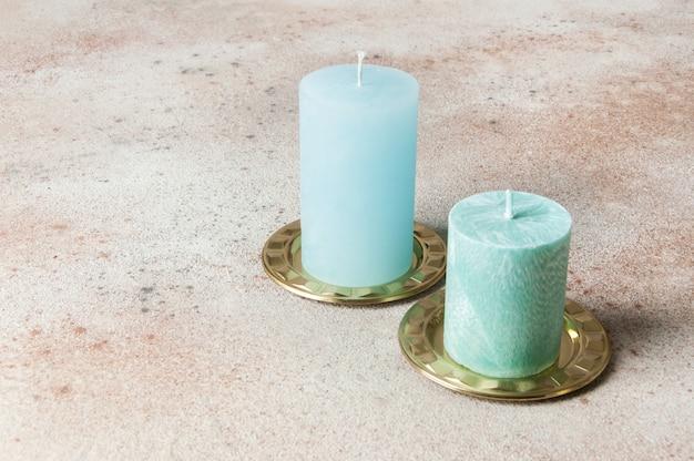 真鍮の燭台、コースター、コンクリートの小皿に青いキャンドル