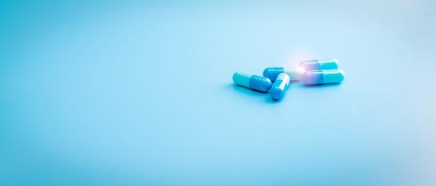 青い背景の上の青いカプセルの丸薬。薬局のバナー。製薬業界。抗生物質カプセルピル。抗生物質耐性。製薬業界。処方薬。薬物研究。
