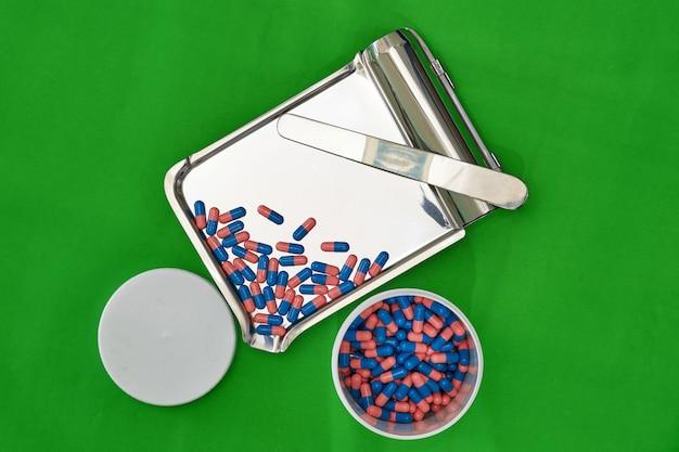 緑色の背景で薬局の店で瓶が付いている皿の青いカプセル