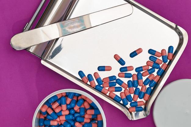 紫色の背景に薬局の瓶が付いている皿の青いカプセル