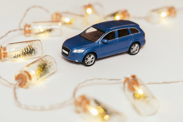 背景にライトが付いている青い車のおもちゃ。花輪