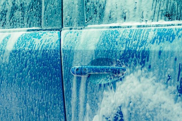 白い石鹸の泡で青い洗車