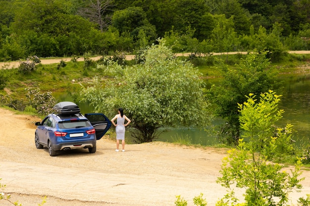 A blue car with a girl with a black roof rack stands against the background of a mountain lake with mountains and clouds.