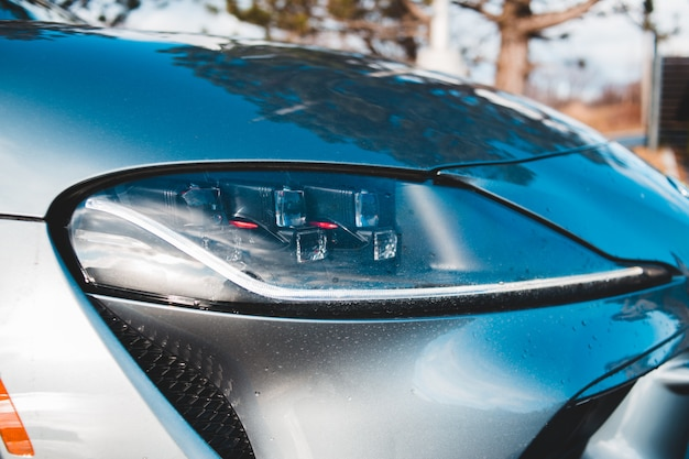 ヘッドライトが付いている青い車をクローズアップ