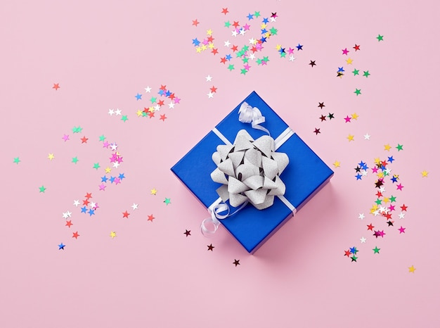 Blue cardboard square box tied up with a white ribbon with a shiny bow and scattered multicolored shiny star-shaped confetti