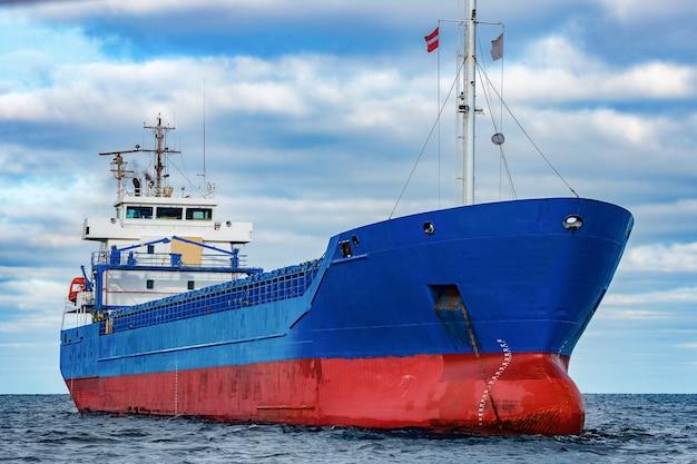 Синий грузовой корабль пришвартован в спокойной воде балтийского моря