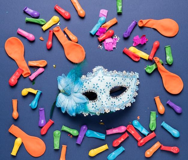 青いカーニバルマスクとカラフルな風船と紙吹雪