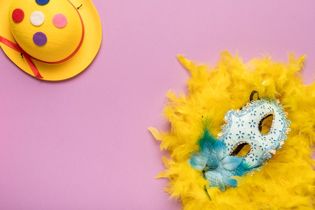 Blue carnival mask with yellow feather boa on pink background