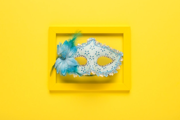 Blue carnival mask in yellow frame