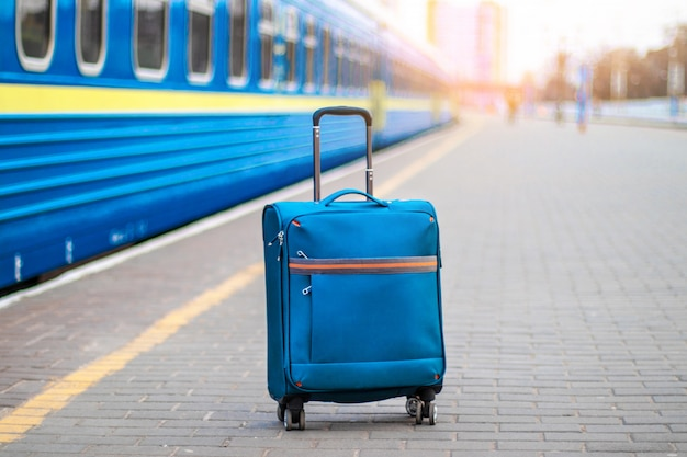 A blue carry-on suitcase with wheels and a metal handle stands on the peron of the station