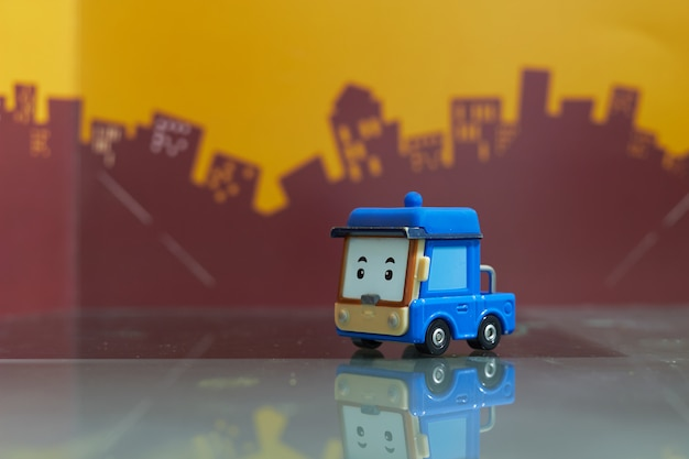 ぼかしの街に青い漫画車のおもちゃセレクティブフォーカス