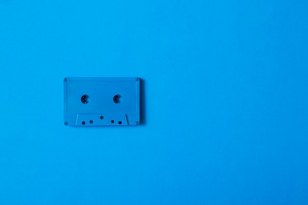 Blue cassette tape on colored background