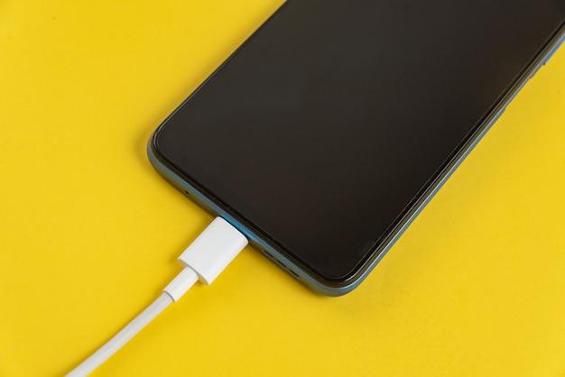 Синий сотовый телефон, подключенный к usb-кабелю типа c - зарядка