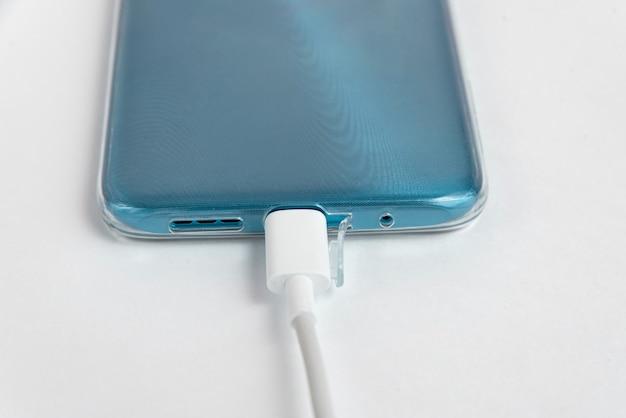 Usb 케이블 유형 c에 연결된 파란색 휴대폰 - 충전 중