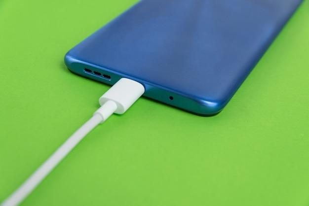 Usbケーブルタイプに接続された青い携帯電話-充電