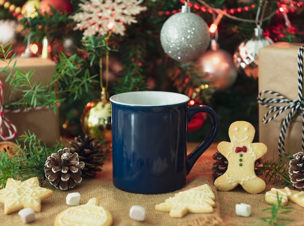 青いセラミックコーヒーカップとクリスマステーブルデコレーション。創造的な広告テキストメッセージまたはプロモーションコンテンツのモックアップ。